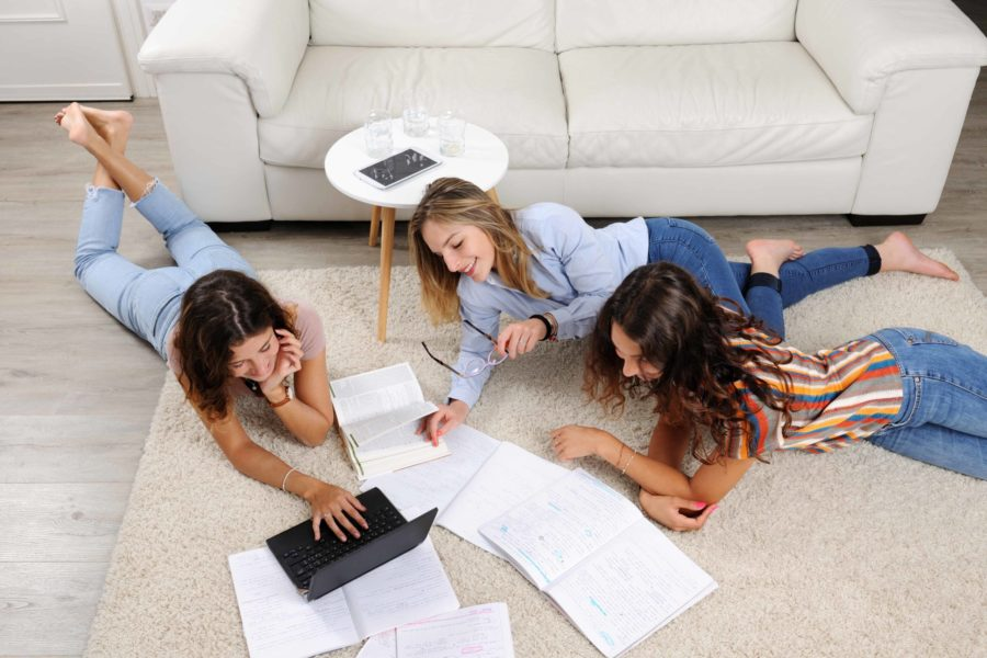 Chicas estudiando en el suelo Habitaciones para universitarios Unihabit scaled 900x600 1