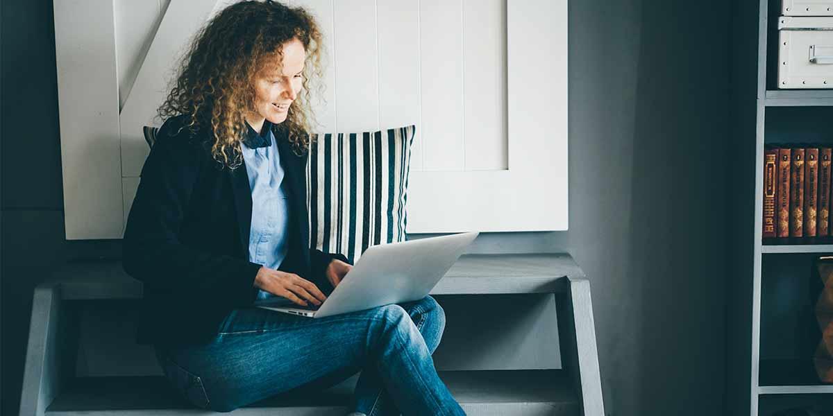 chica sentada en piso con portatil Habitaciones para universitarios UNIHABIT