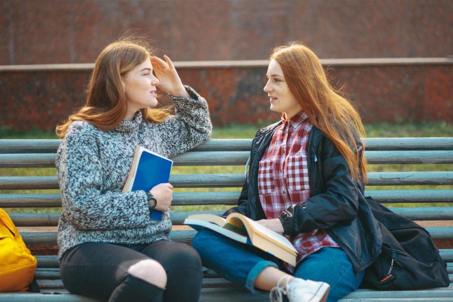 dos chicas hablando en banco Aprender un nuevo idioma en Barcelona Unihabit scaled 900x600 1